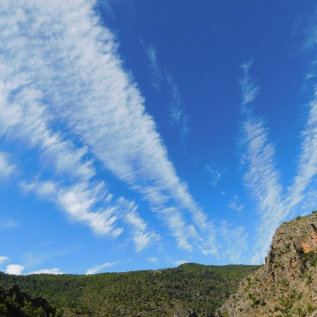 A beautiful blue sky with plane vapour trails streaking across from the viewer to the top of a mountain. In the foreground on the right, part of the mountain is closer, grey-brow rock speckled with greenery.