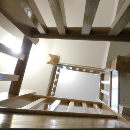 Looking upwards through a hall that passes three flights of stairs.