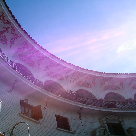 A section of a wide, beautifully ornate balcony that surrounds the upper level of a round, white building, seen from the inside, looking upwards. Below is a row of shuttered windows and some flowers are visible in the corner. Above, is a blue semi-circle of sky with the sun shining down and casting bright rays across the building.